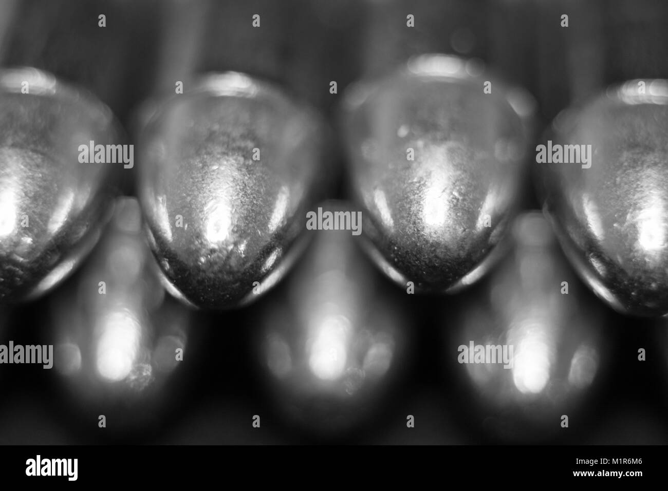 A black and white macro of 9mm Luger rounds in a row. - Stock Image