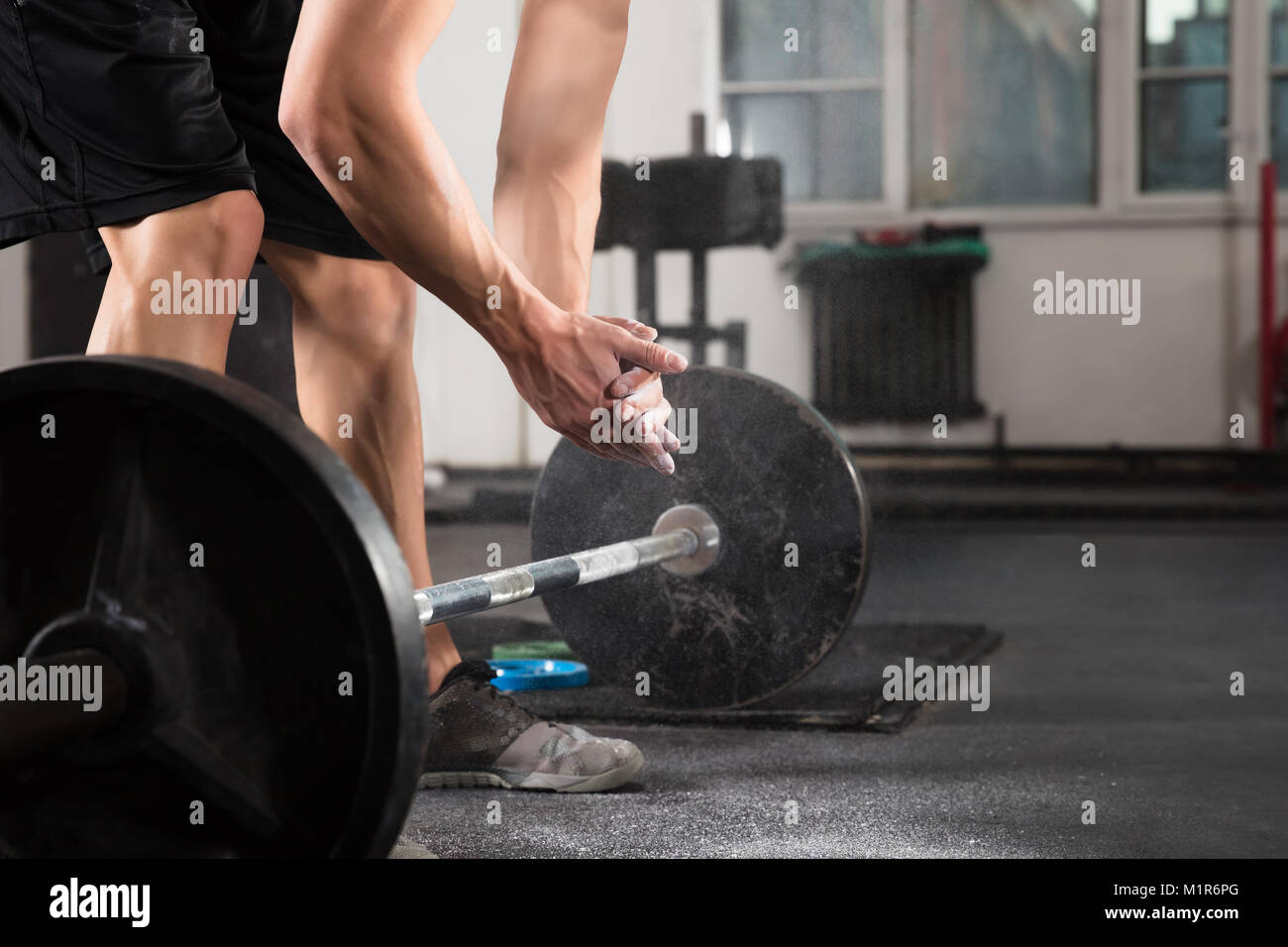 Weightlifter Hand Applying Talc Powder Before Doing Exercise With Barbell In Gym - Stock Image
