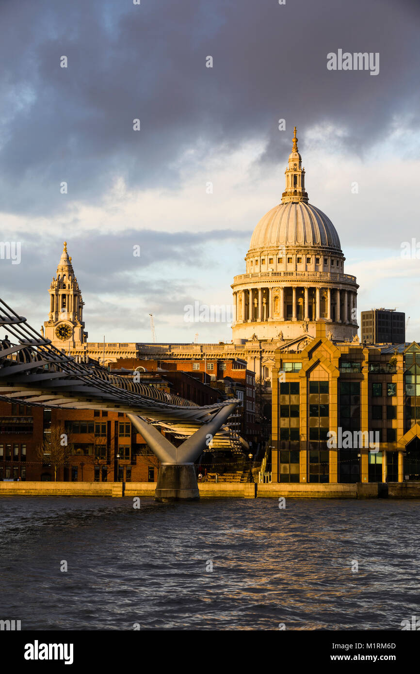 St. Paul's Cathedral and the Millenium Bridge with gorgeous late afternoon light illuminating the dome of St - Stock Image