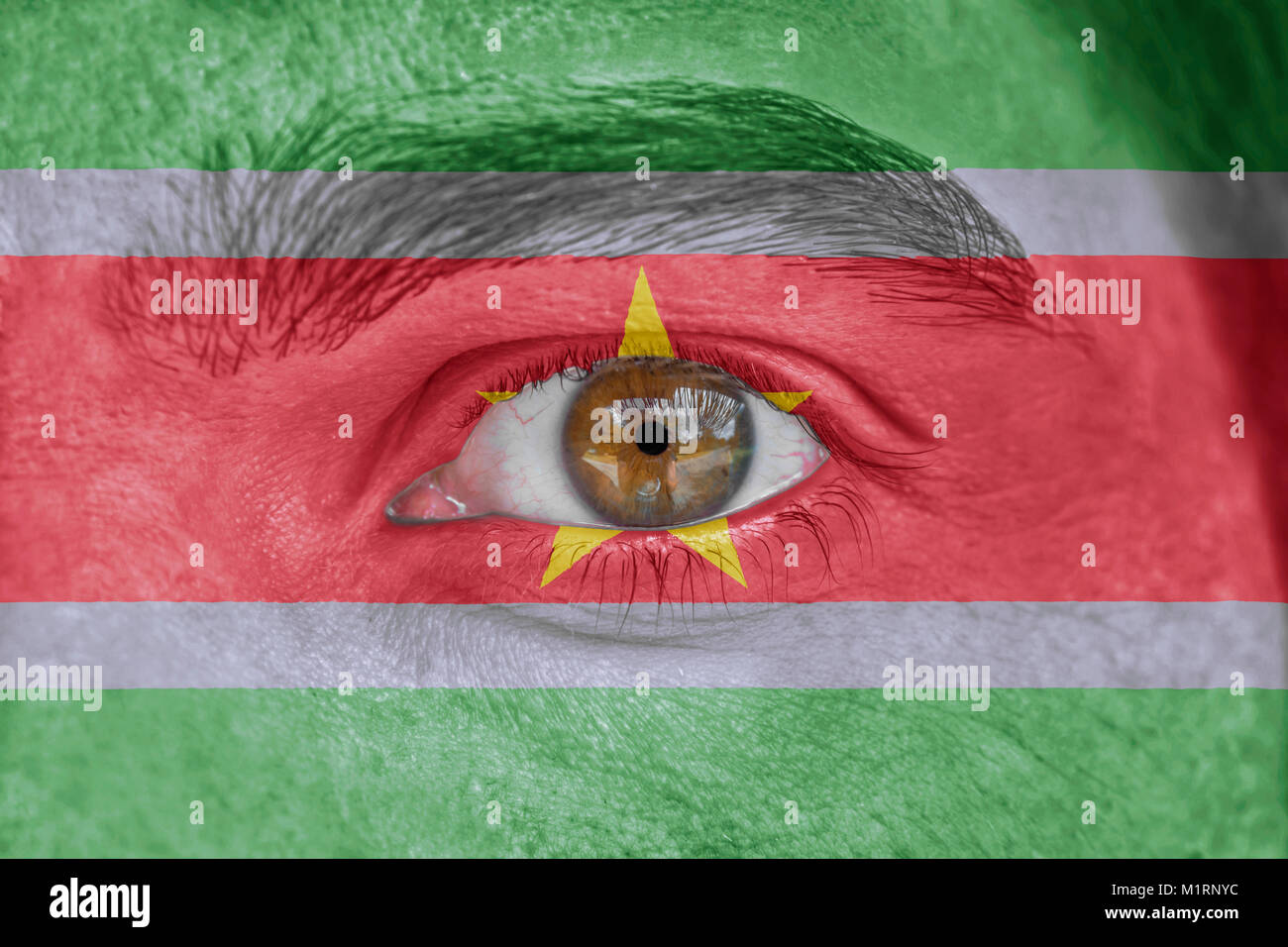 Human face and eye painted with flag of Suriname - Stock Image