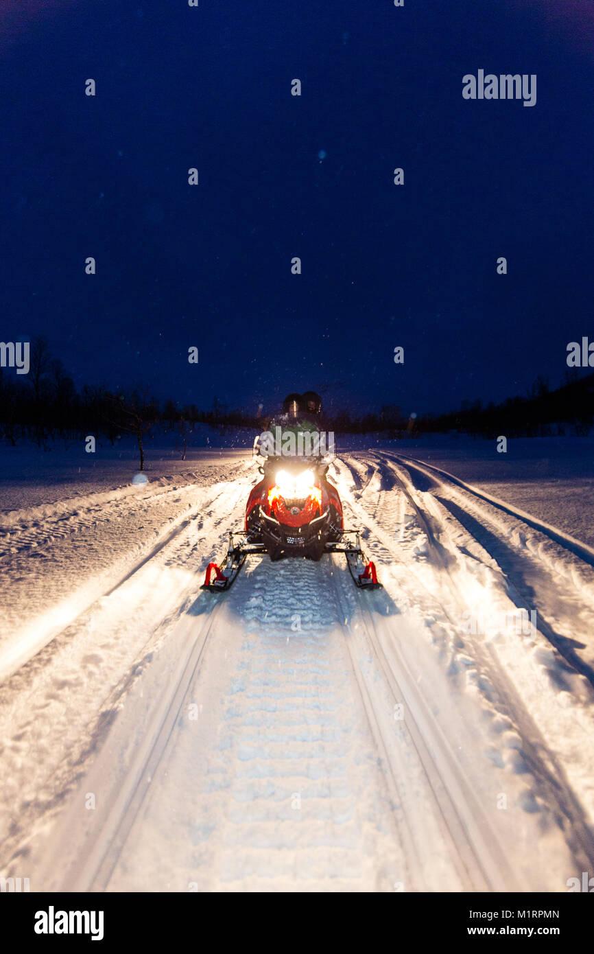 Skibotn, Norway. Snow mobiling action shot at night. - Stock Image