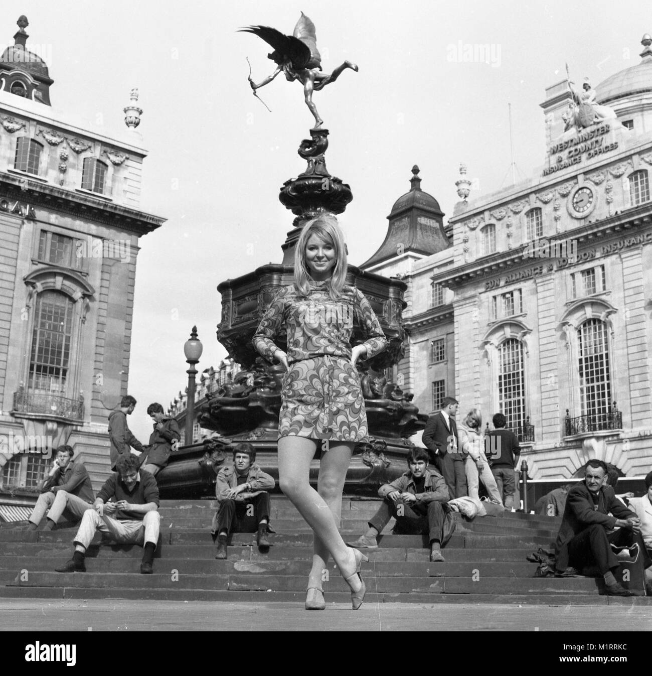 A model poses in a mini dress outdoors in London's Piccadilly near the statue of Eros in circa 1968 wearing a colourful mini-dress.   Photo by Tony Henshaw Stock Photo