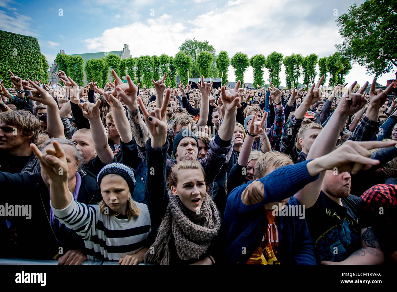 Heavy metal fans show The sign of the horns with their hands at a live concert with the French heavy metal band - Stock Image