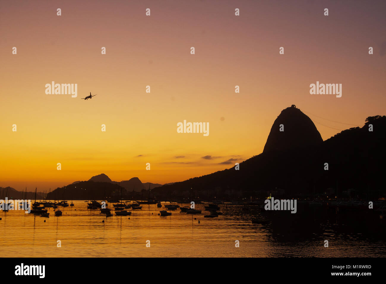 Airplane arriving an passing near the Sugarloaf at sunrise, Rio de Janeiro, Brazil - Stock Image