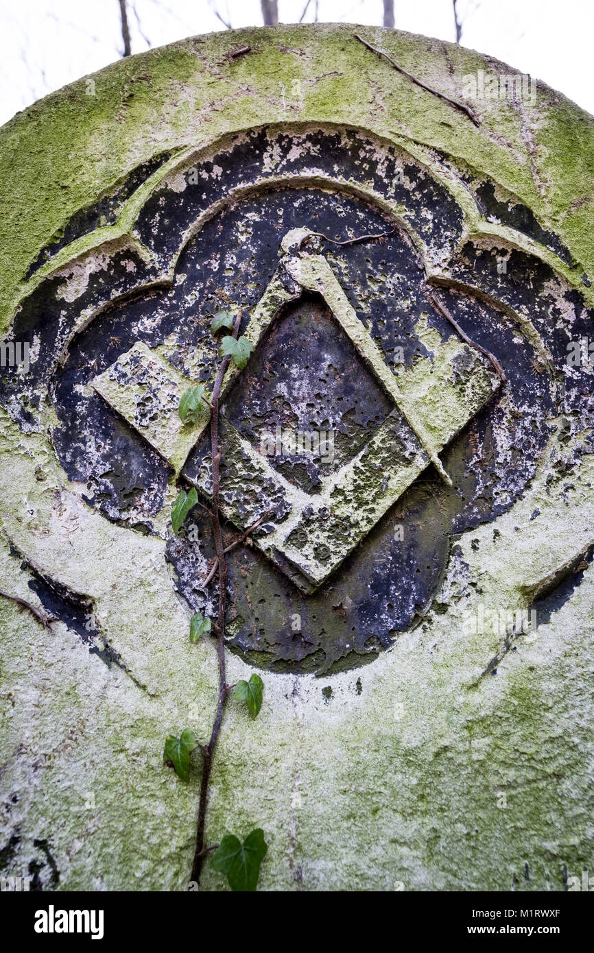 A Masonic gravestone in Tower Hamlets Cemetery featuring the Freemason's signature square and compass emblem etched - Stock Image