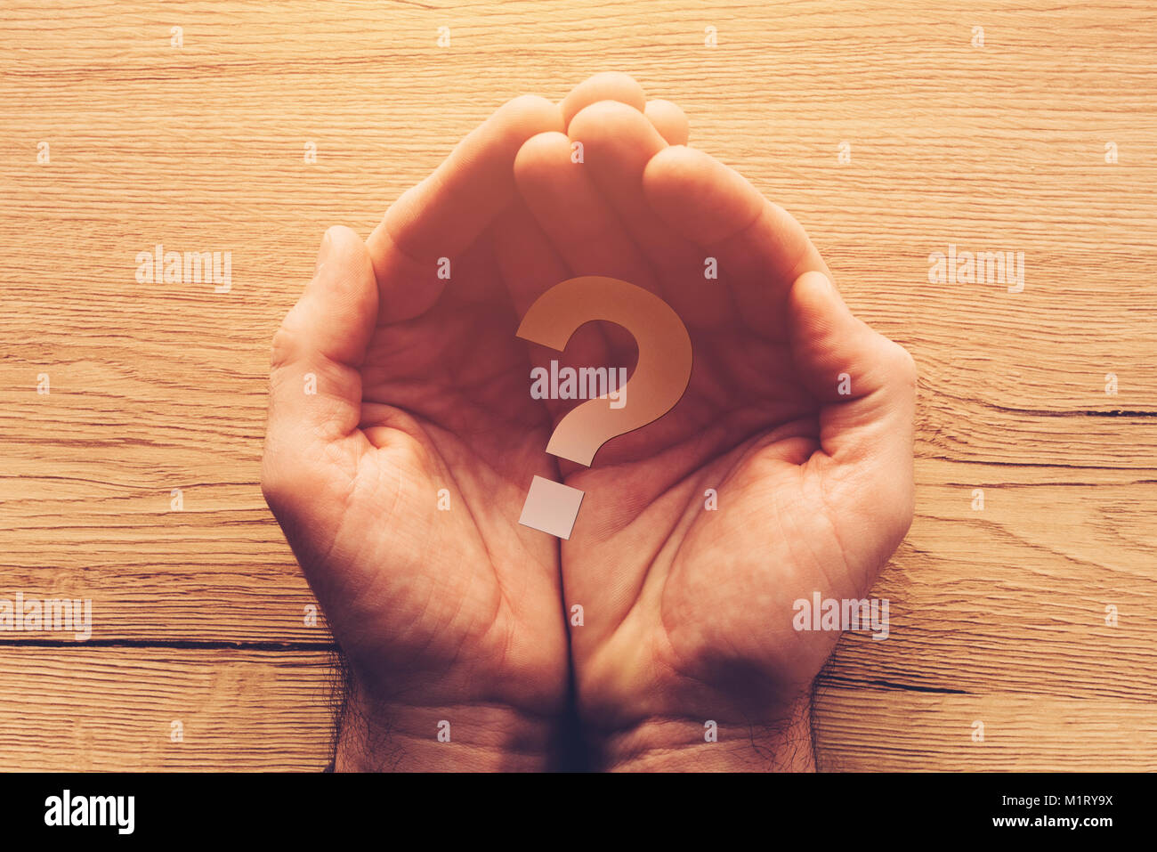 Question mark in cupped male hands, looking for the answer on delicate questions, overhead view - Stock Image
