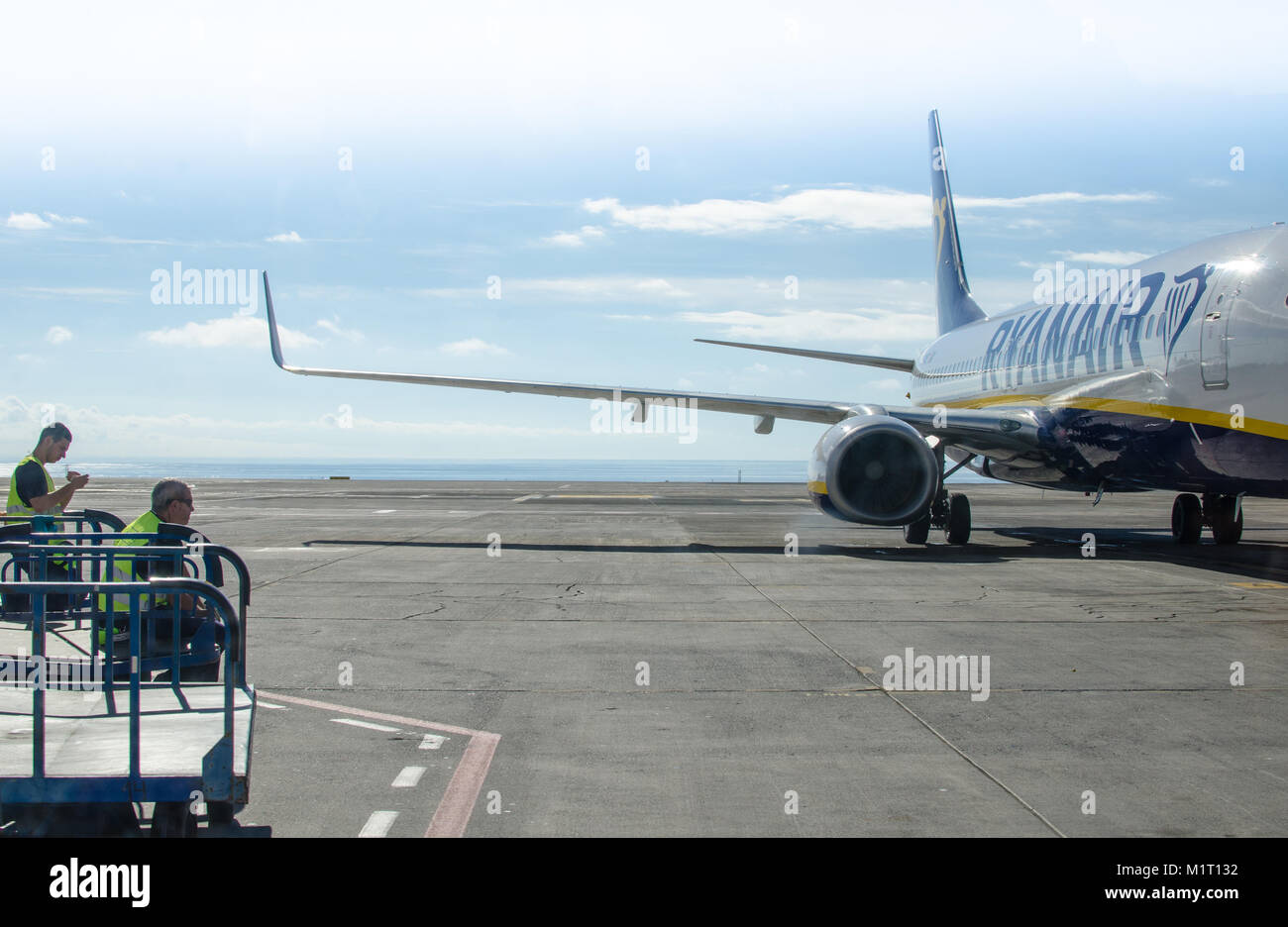 Baggage handlers wait on a taxiing Ryanair Boeing 737 at Tenerife-South Airport, Canary Islands, Spain - Stock Image