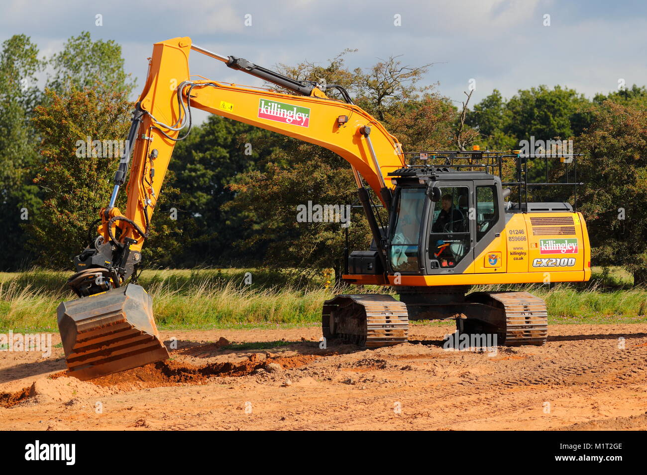 An excavator trials a new rotating bucket attachment on a new section of road being built in Doncaster which leads - Stock Image