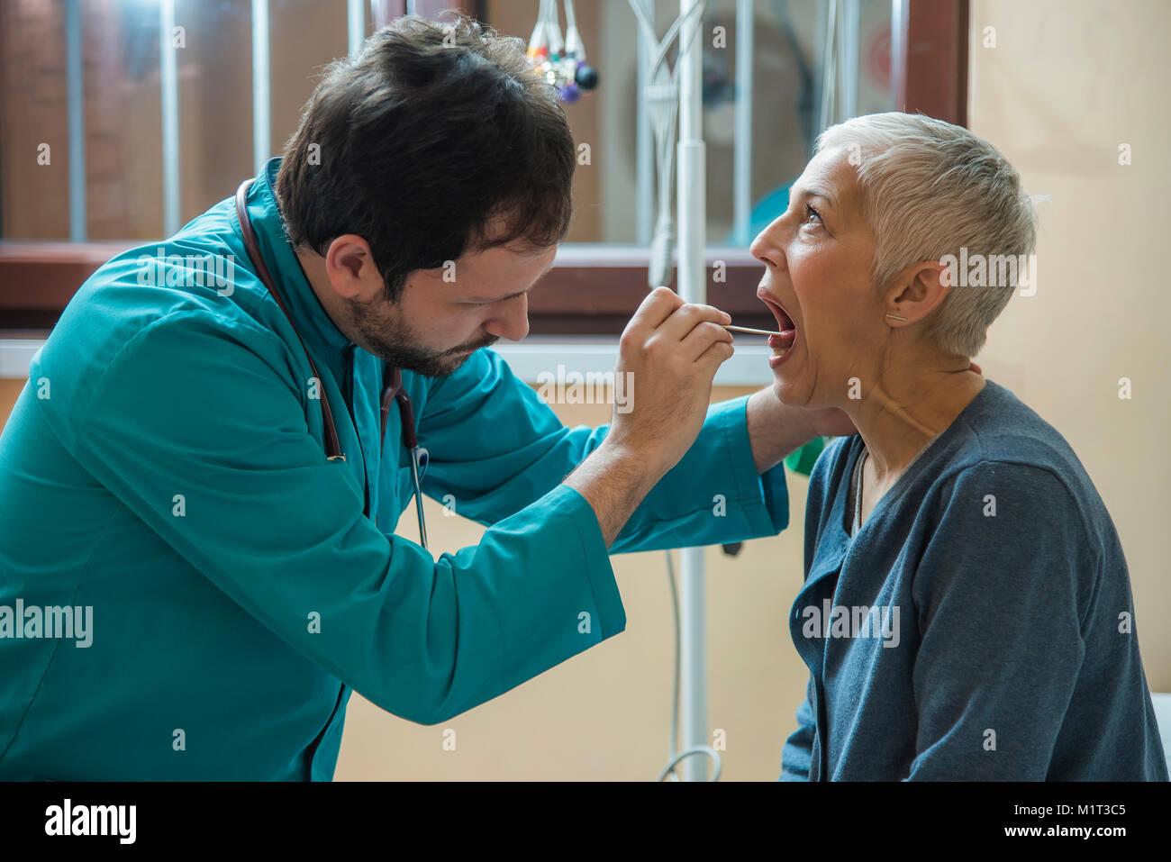 Laryngitis or tonsil problem a senior woman is checking with her doctor - Stock Image