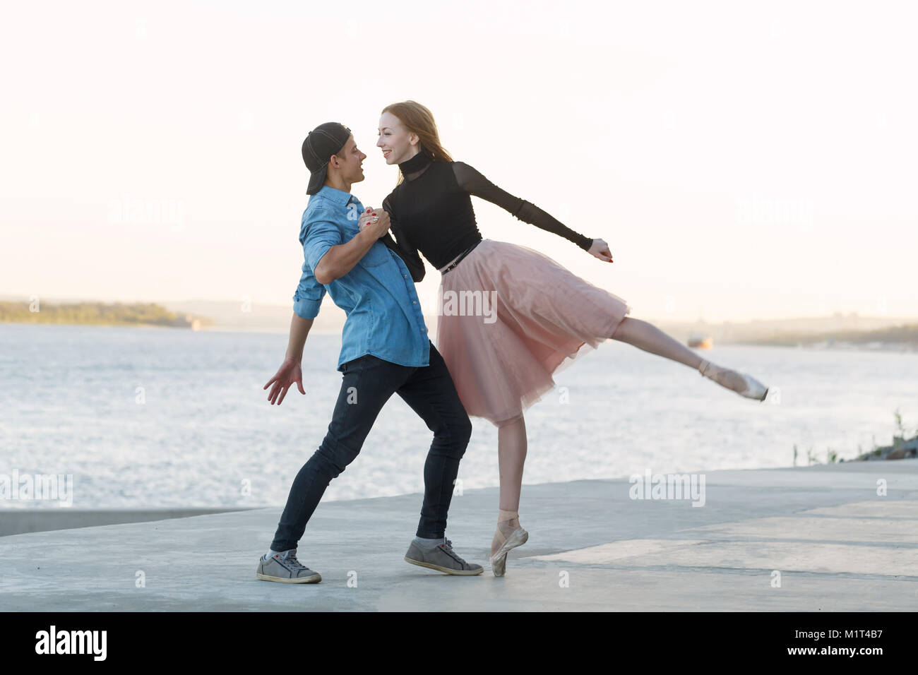 A slender ballerina dances with a modern dancer. Dating lovers. Passion and romance of dance. He holds her hand. - Stock Image