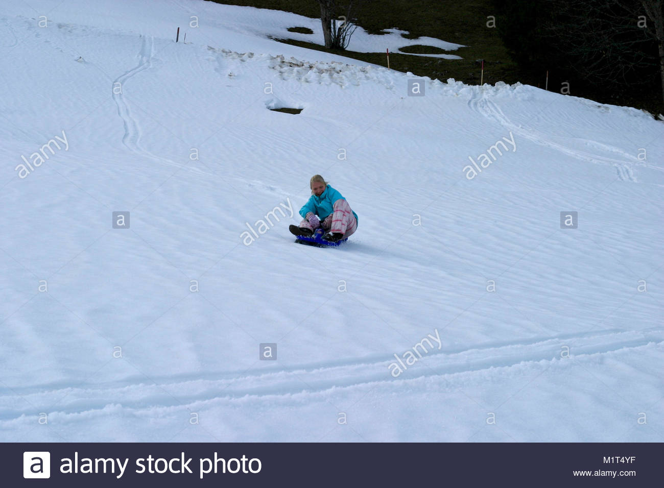 Young girl is sliding downhill and laughing; Switzerland - Stock Image