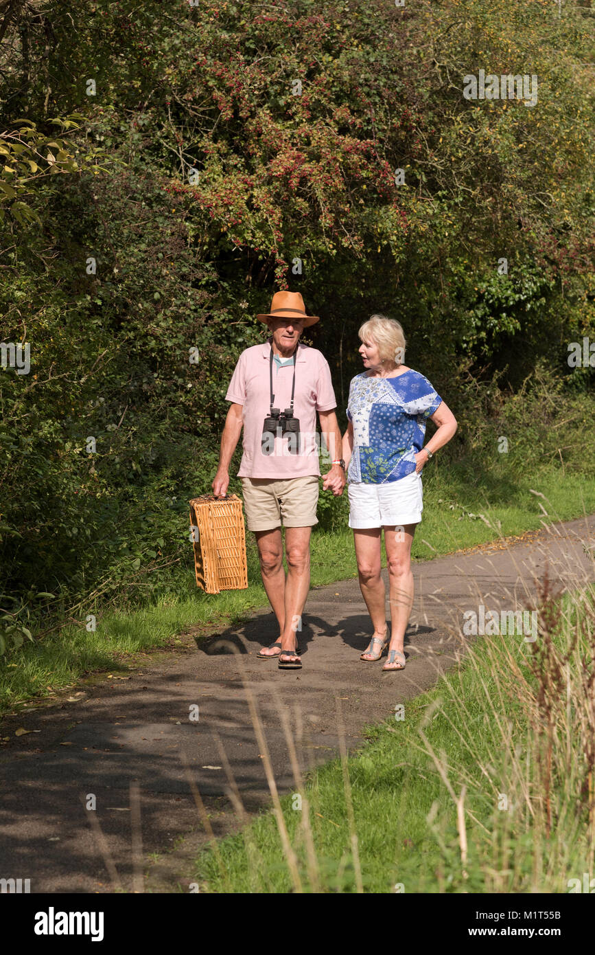 Elderly couple walking along the towpath of the Wilts and Berks canal near Swindon UK. - Stock Image
