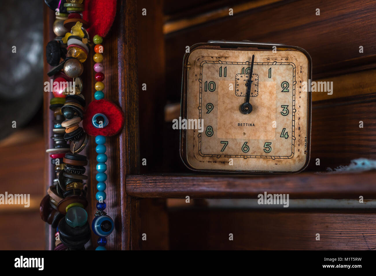 Old antique clock and beads on wooden shelf Stock Photo
