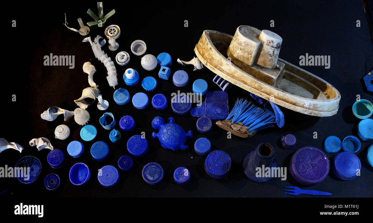 A toy boat sails the heaving sea of plastic trash. - Stock Image