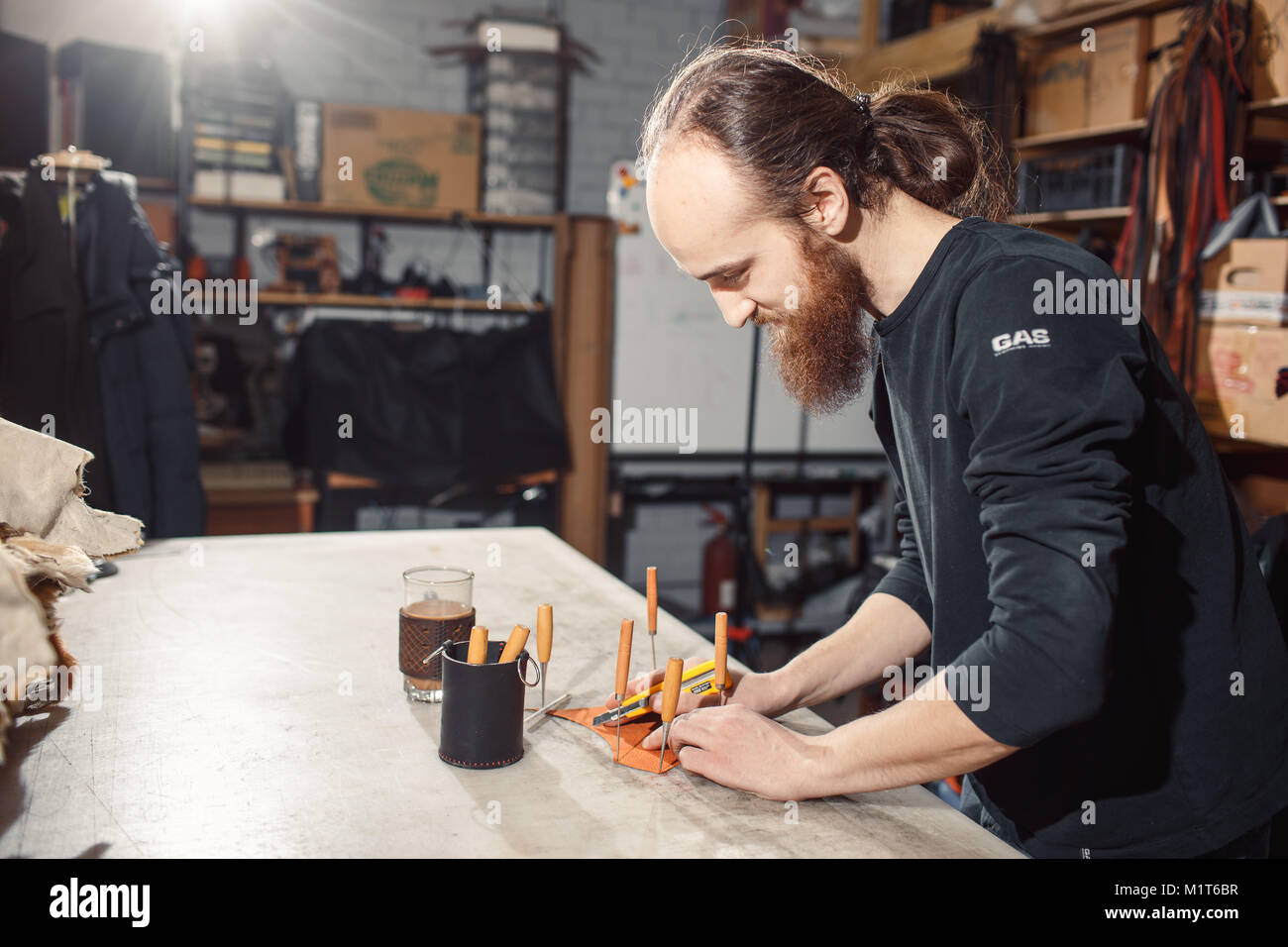 Working process in the leather workshop. Tanner in old tannery. - Stock Image