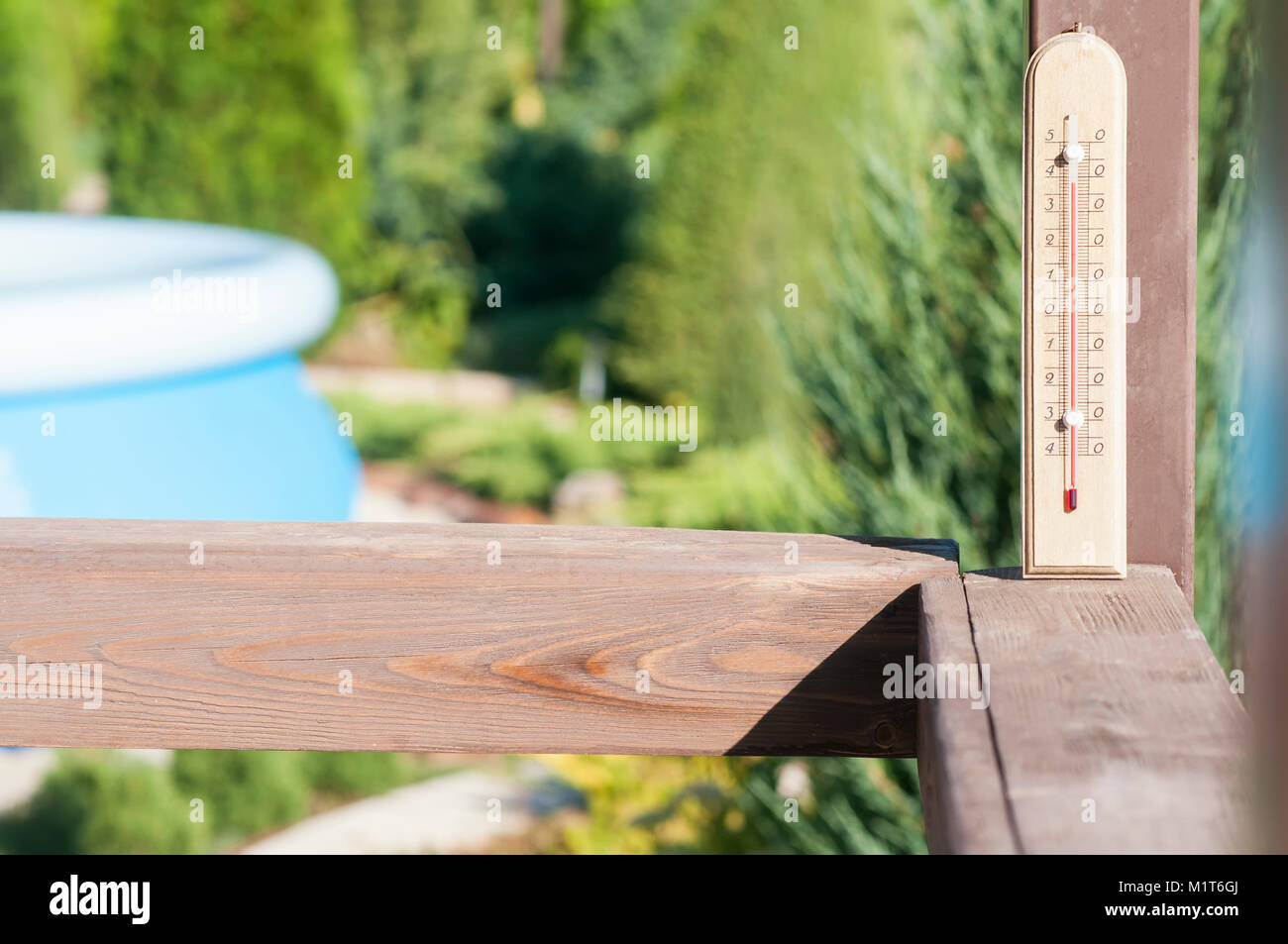 Wooden garden thermometer on a street in a country house - Stock Image
