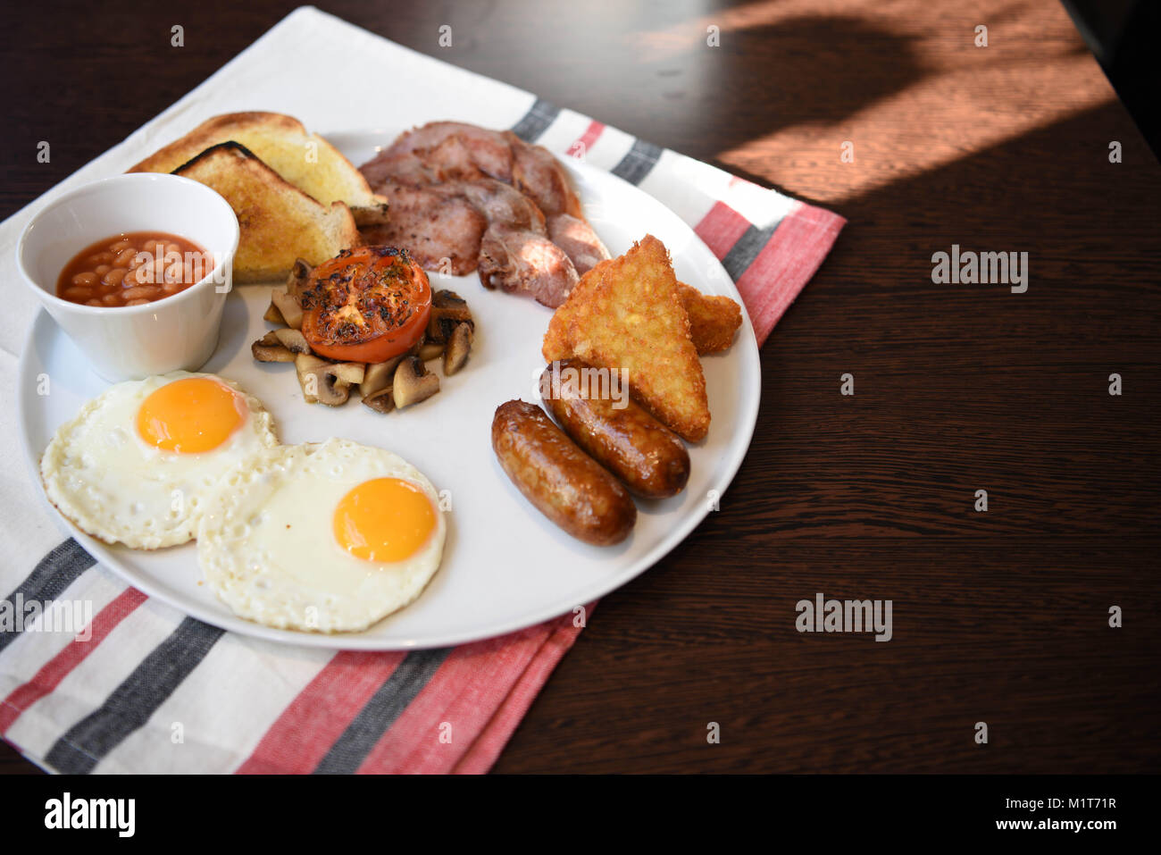traditional full English breakfast served and ready to eat with fried eggs sausages mushrooms bacon beans toast - Stock Image