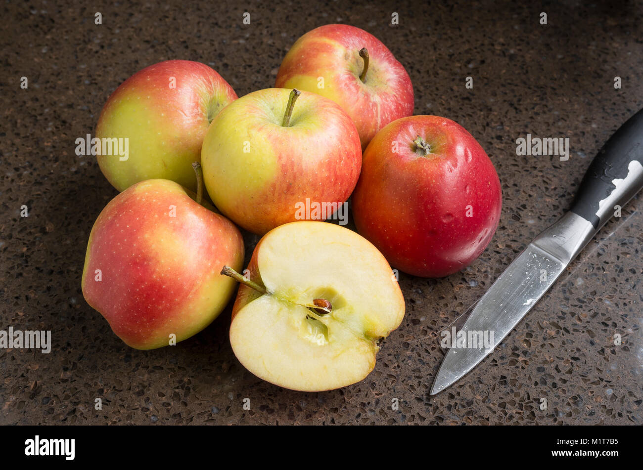 Selection of shop-bought Kansi apples variety Nicoter characterised by coloour, taste and crispness with one sliced Stock Photo
