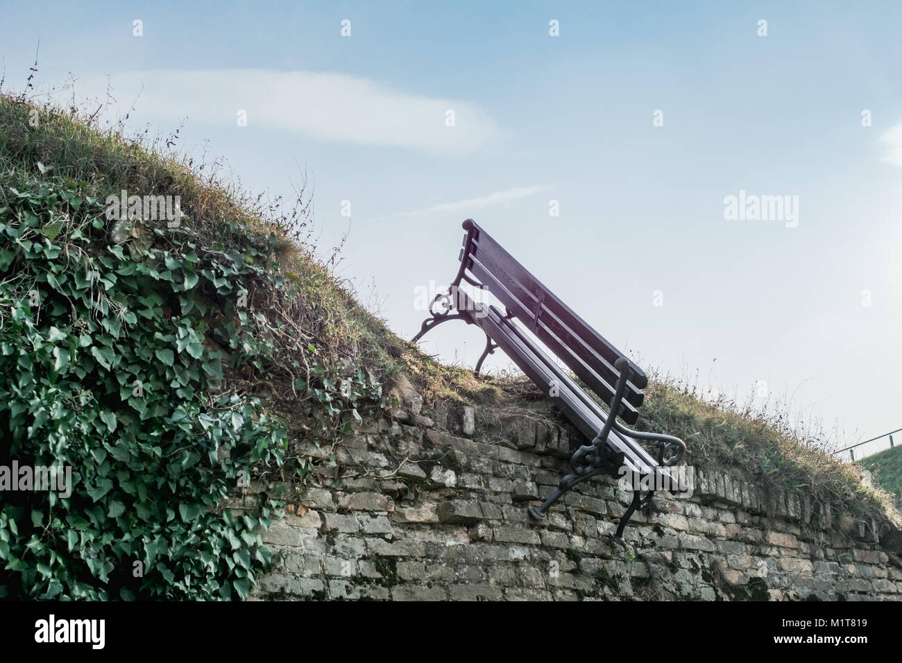 Vandalized wooden bench hanging on the fortress wall - Stock Image