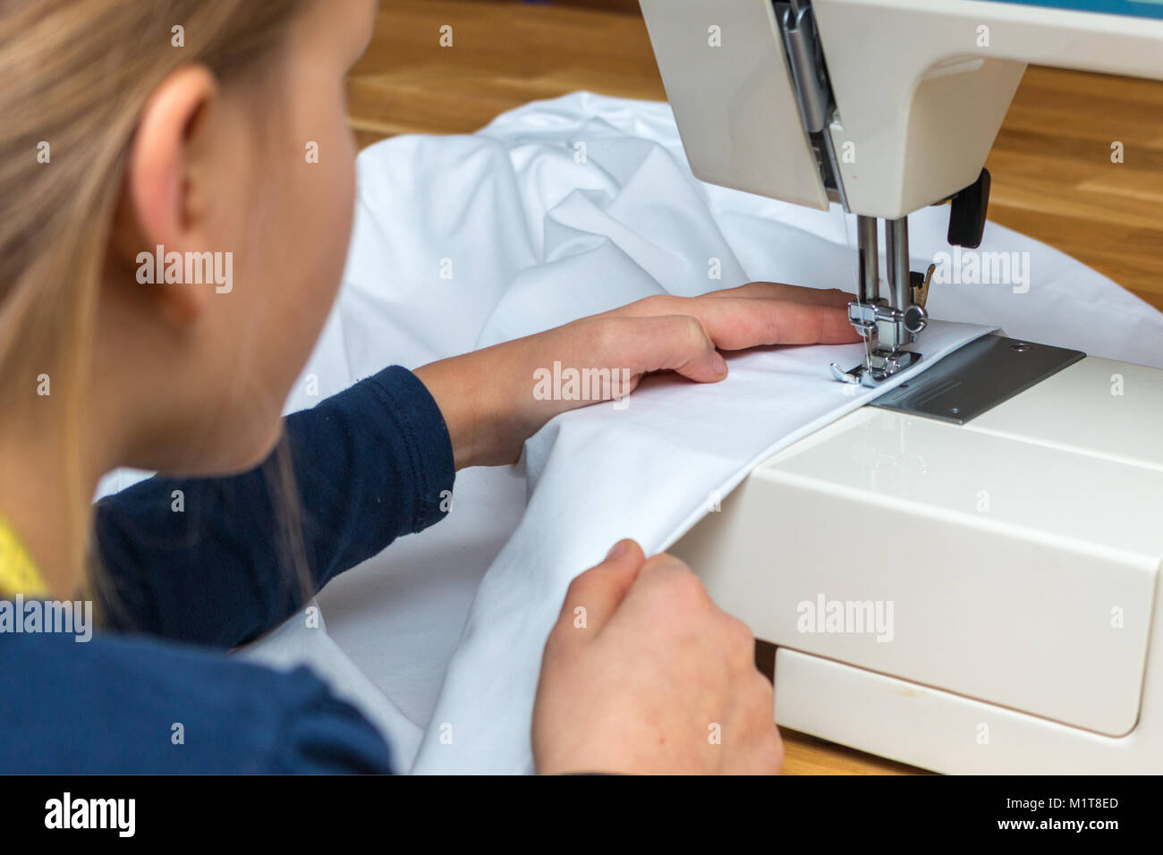 A 8 year old girl is sewing a white textil Stock Photo