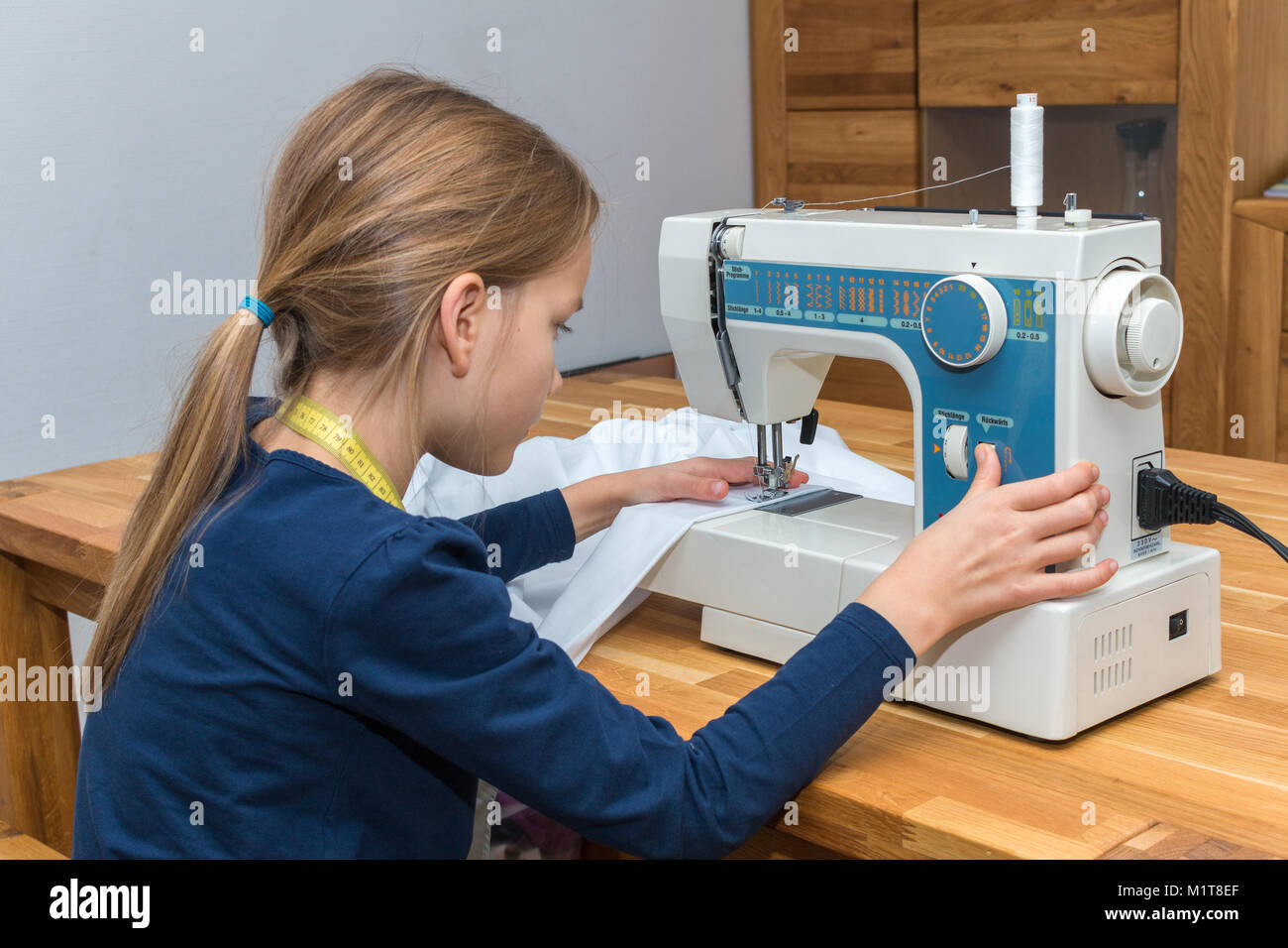 A 8 year old girl is sewing a white textile. Right hand presses the rewind button Stock Photo