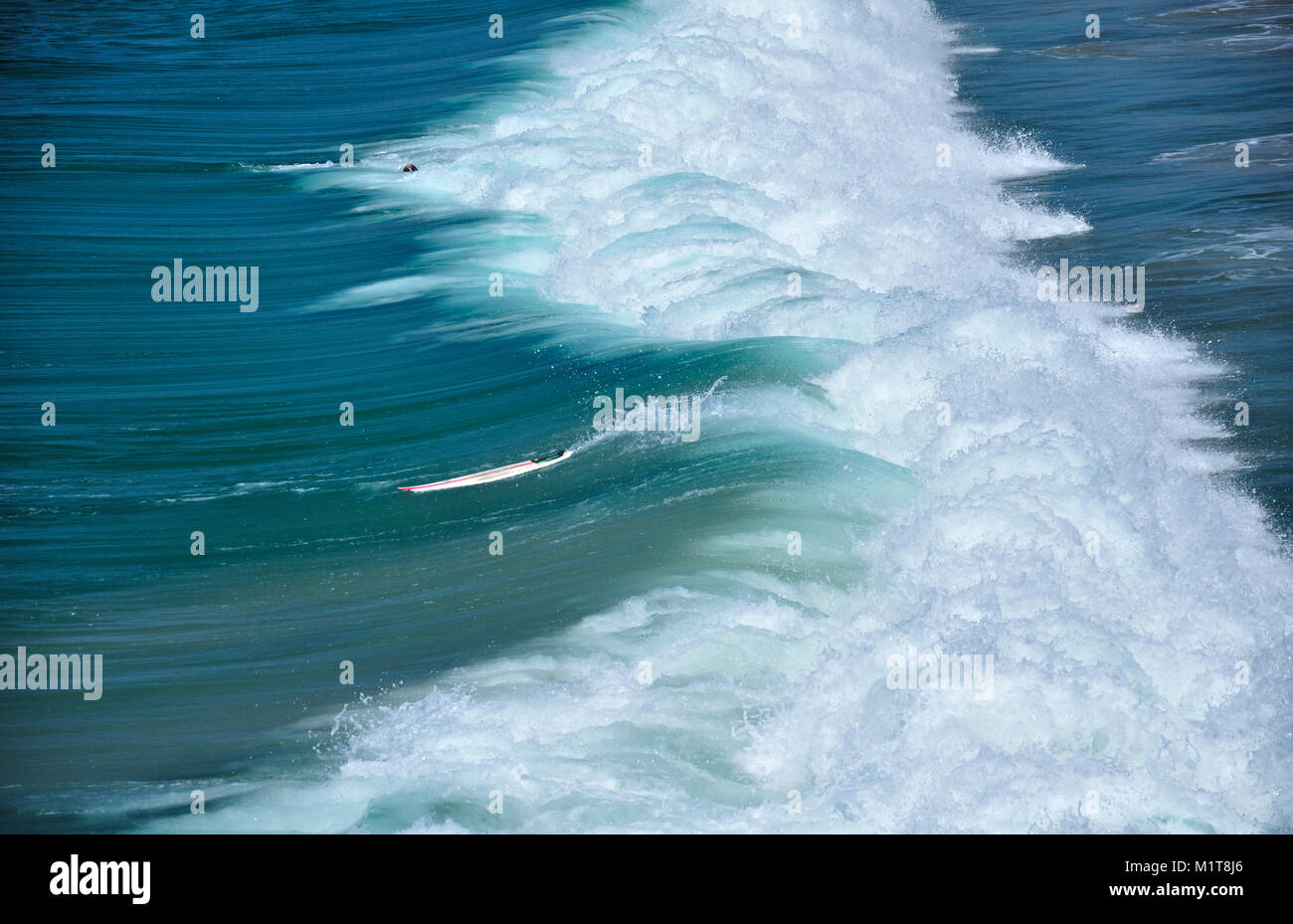 A surfer wiping out in the Pacific Ocean waves crashing down on Manhattan beach california on a sunny day on the - Stock Image