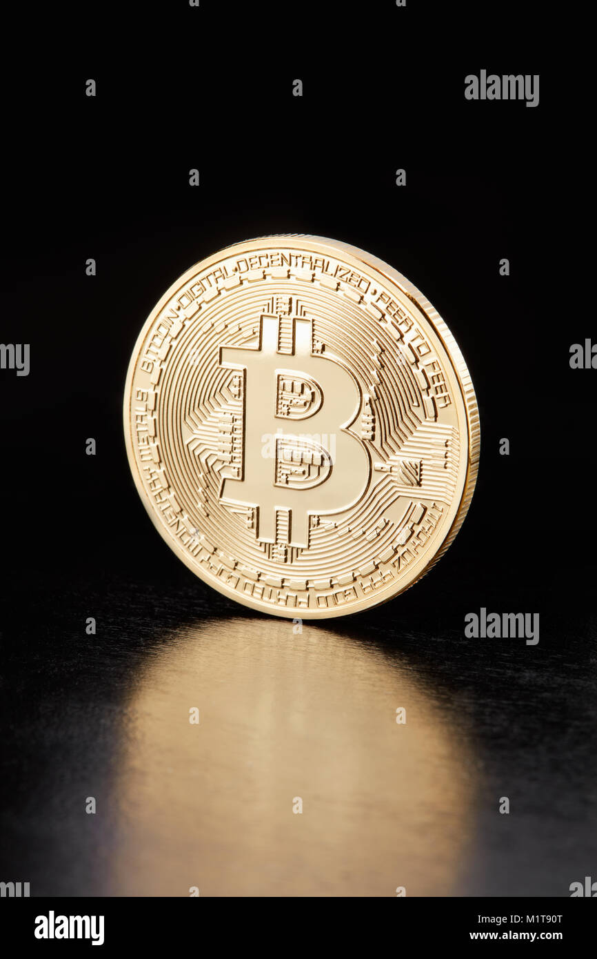 Golden Bitcoin, cryptocurrency coin on black, clipping path - Stock Image