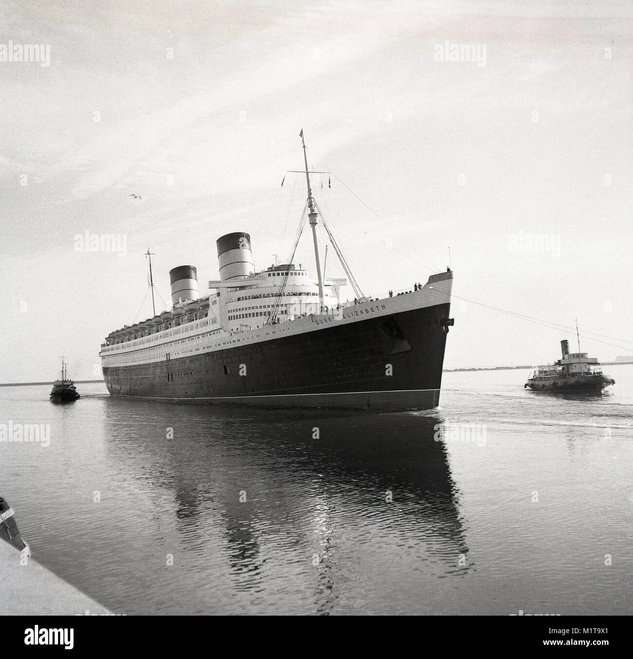 1950s, historical, tugboats pull the RMS Queen Elizabeth ocean liner into the calm waters of Southampton docks, - Stock Image