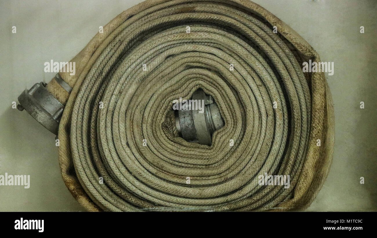 Spiral fire hose in place dirty - Stock Image