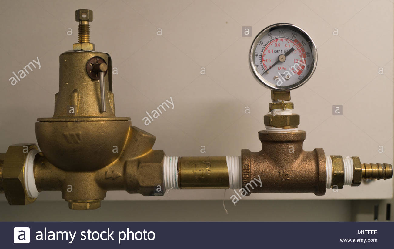 A pressure gauge and other objects on a brass pipe in a research lab. - Stock Image