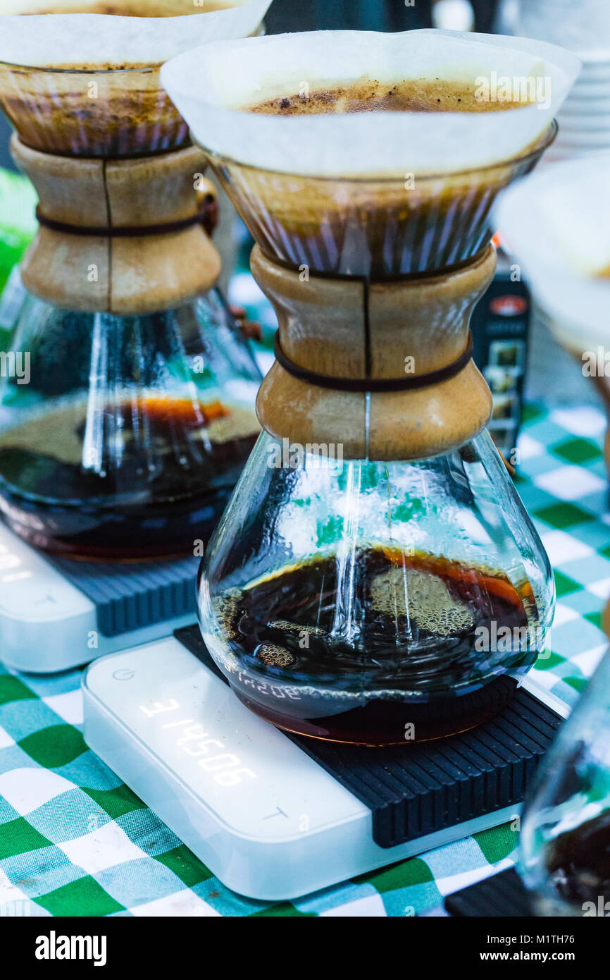 Pour over coffee drips in artisan glass brewers sitting on electronic scales while outdoors on a picnic table - Stock Image