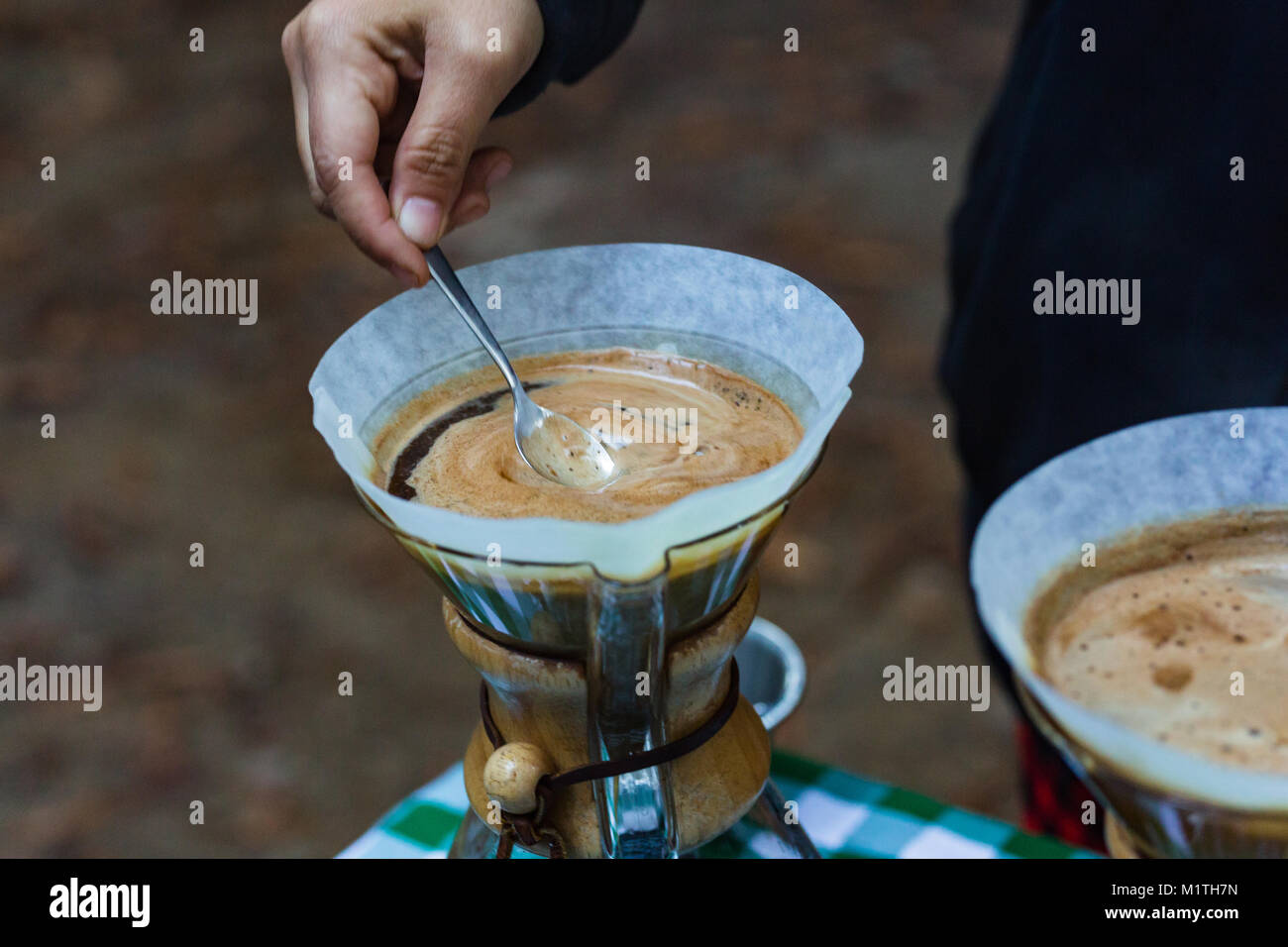 Barista stirs pour over coffee in artisan glass brewer while outdoors - Stock Image