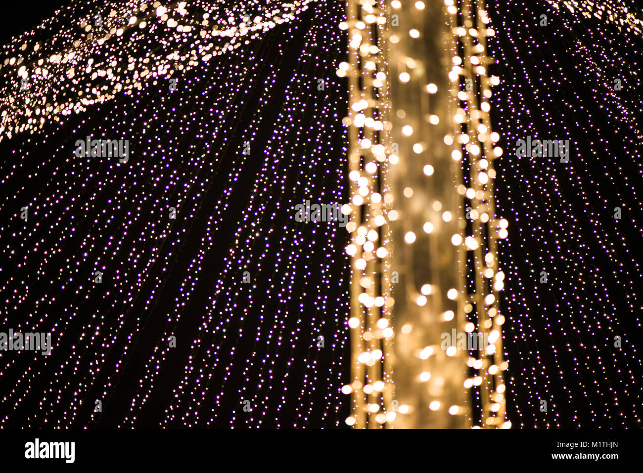 Abstract Christmas tree, colorful, blurry background. Glowing and sparkling lights in city center in Christmas market Stock Photo
