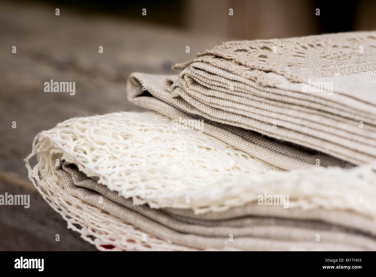 Shot of linen tablecloths, towels and napkins with grey and white lace trim, pine cone, flowers and wheat - Stock Image