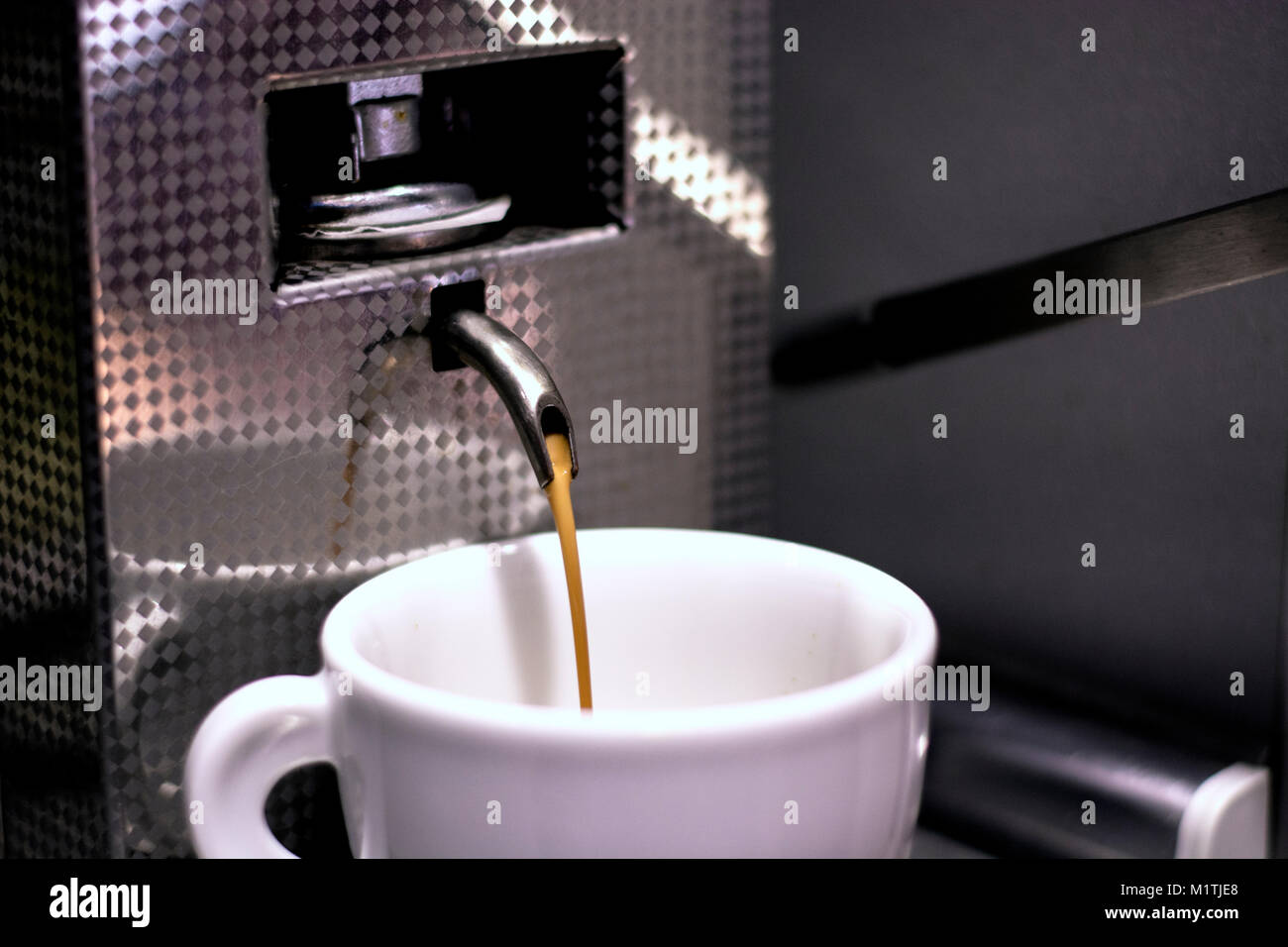 Espresso pouring in coffee cup - Stock Image