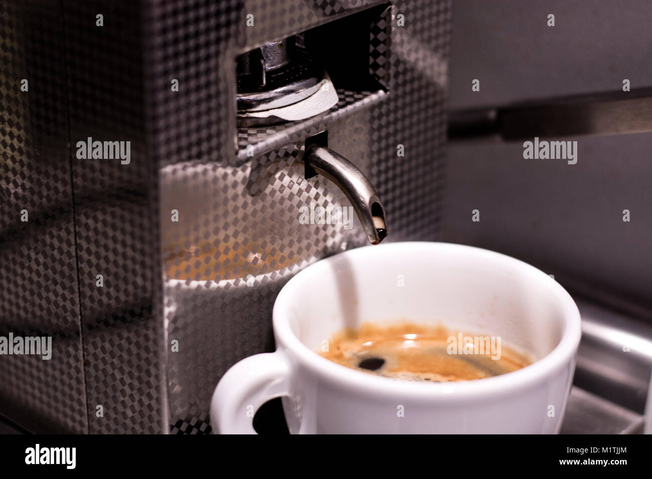 White cup of coffee with coffee maker - Stock Image