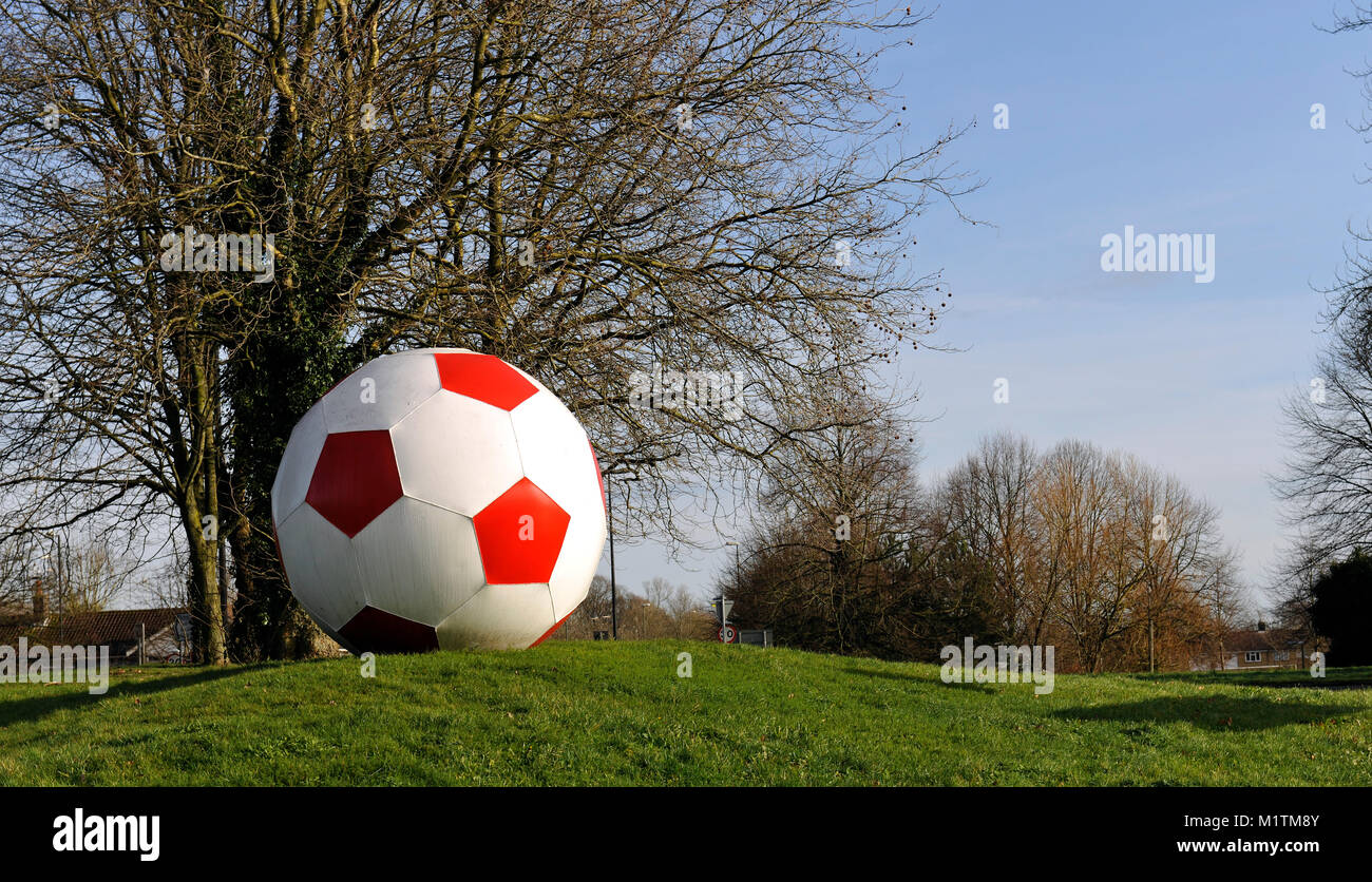 Giant football on street roundabout besides Crawley Town Football Stadium, Crawley, West Sussex, England, UK. - Stock Image
