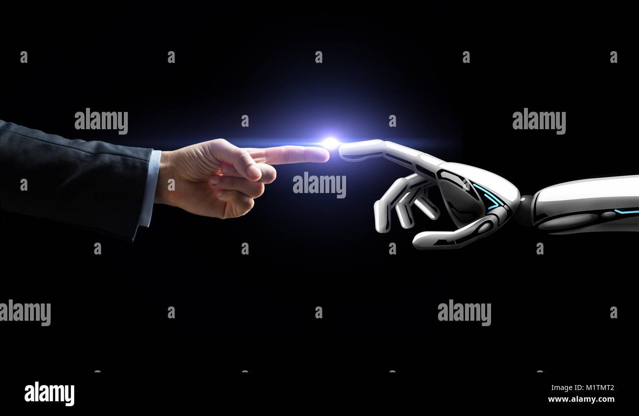 robot and human hand flash light over black - Stock Image