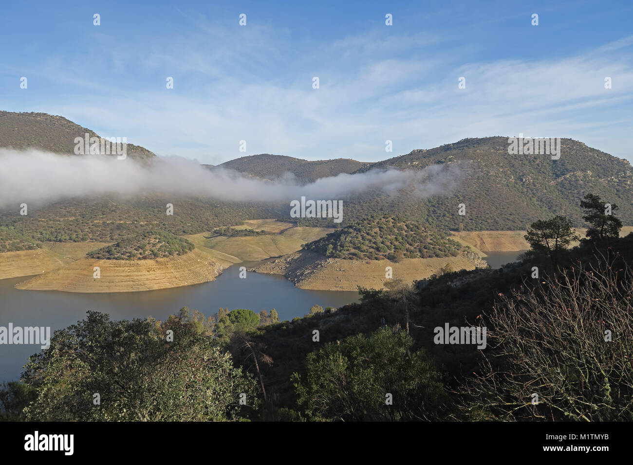 view over reservoir with low water level and bank of cloud  Embalse del Jandula, Parque Natural Sierra de Andujar, - Stock Image