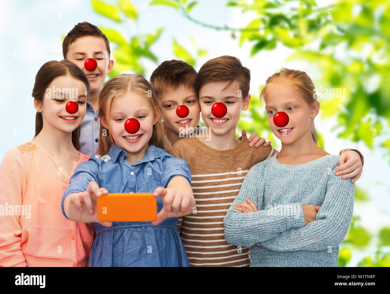 kids taking selfie with smartphone at red nose day - Stock Image