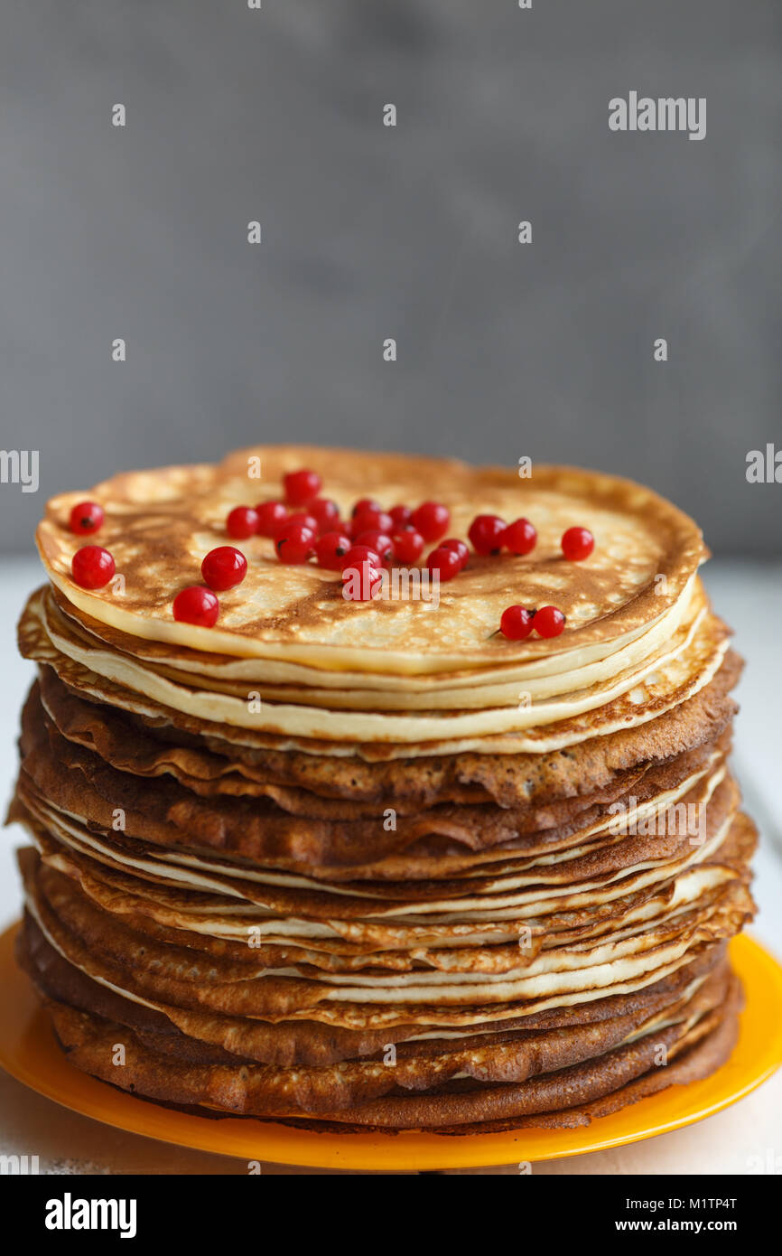 High stack of classic Russian thin pancakes with red currant berries . Rustic style. Traditional for the Russian - Stock Image
