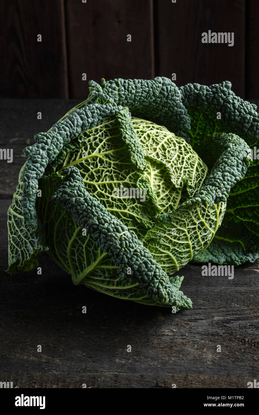Savoy cabbage on a dark wooden table. - Stock Image