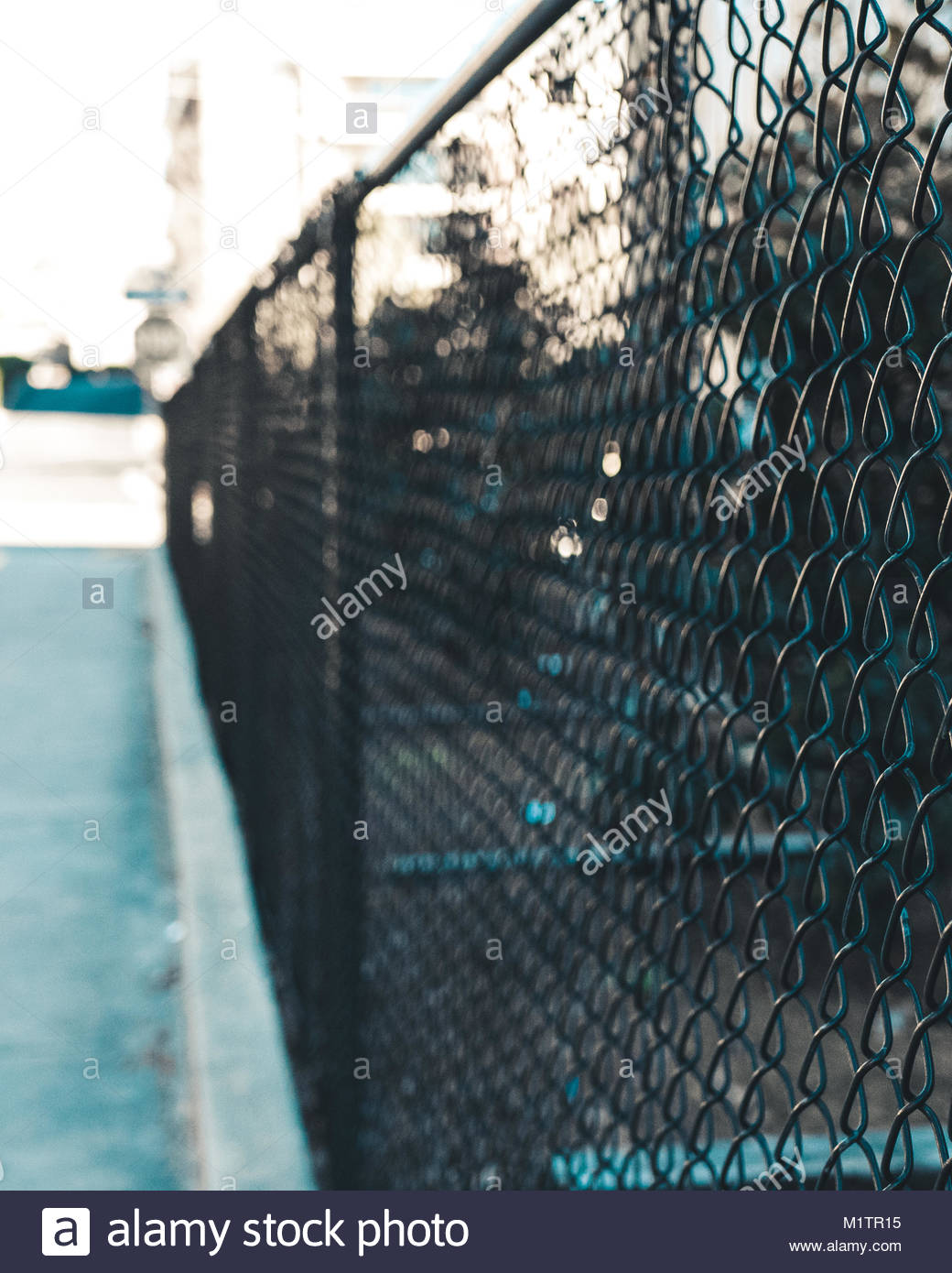 A black chain link fence with a bokeh background parallel