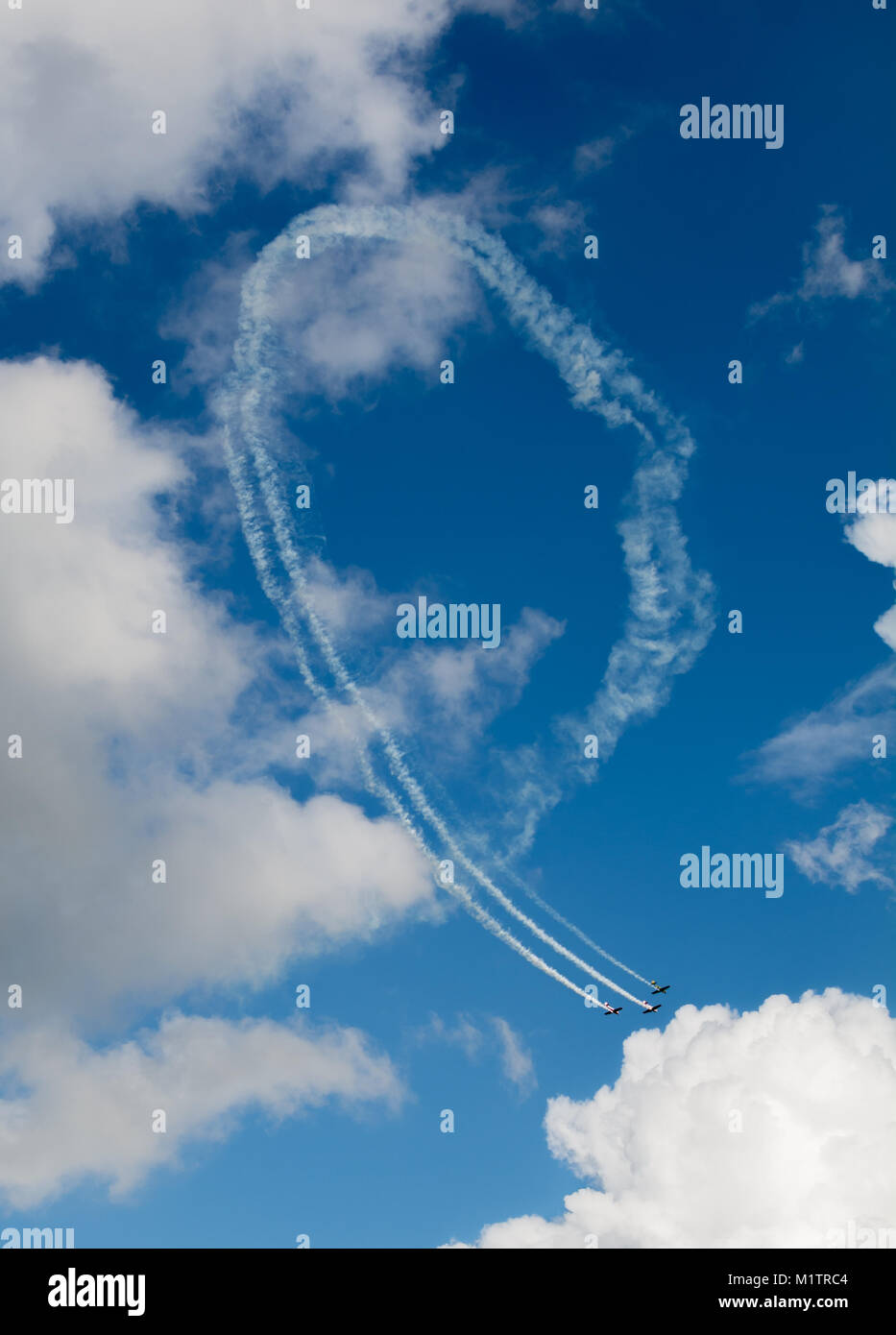 Aerobatic maneuver in a blue sky - Stock Image