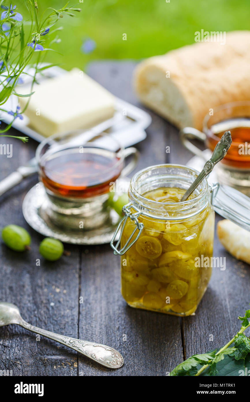 Green gooseberry jam on a wooden table - Stock Image