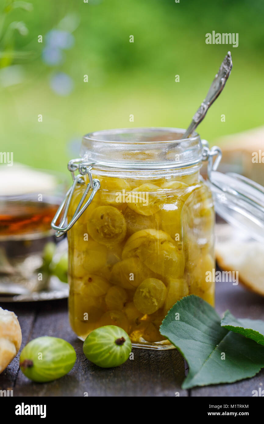 Close view of gooseberry jam in a jar on a wooden table - Stock Image