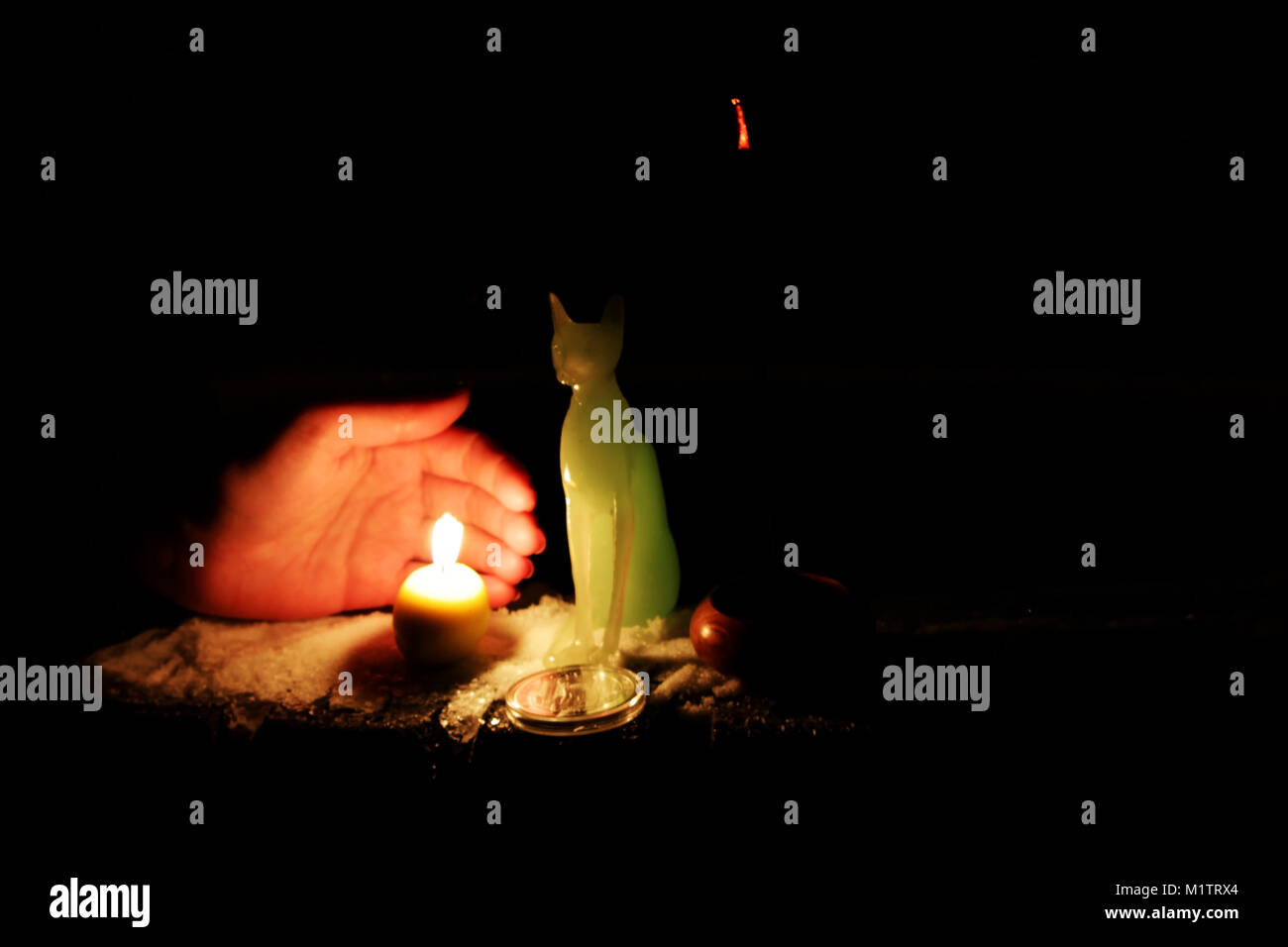 a ritual for the fulfillment of desires with a full moon on the street, with a statue and a candle. January 31, - Stock Image