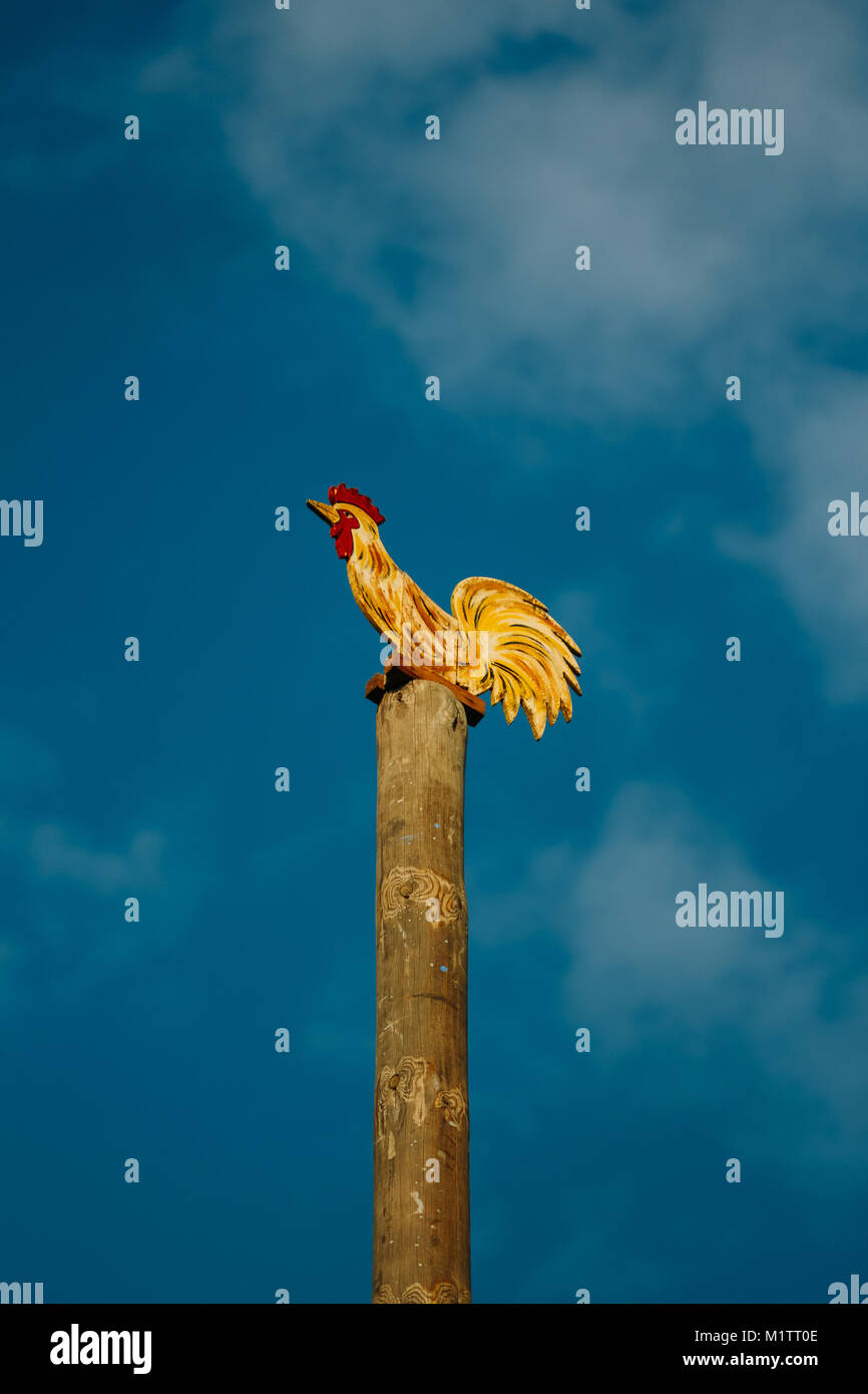 Wooden pole with a large ornament in the form of a rooster on top. Post competition at the national folk festival - Stock Image