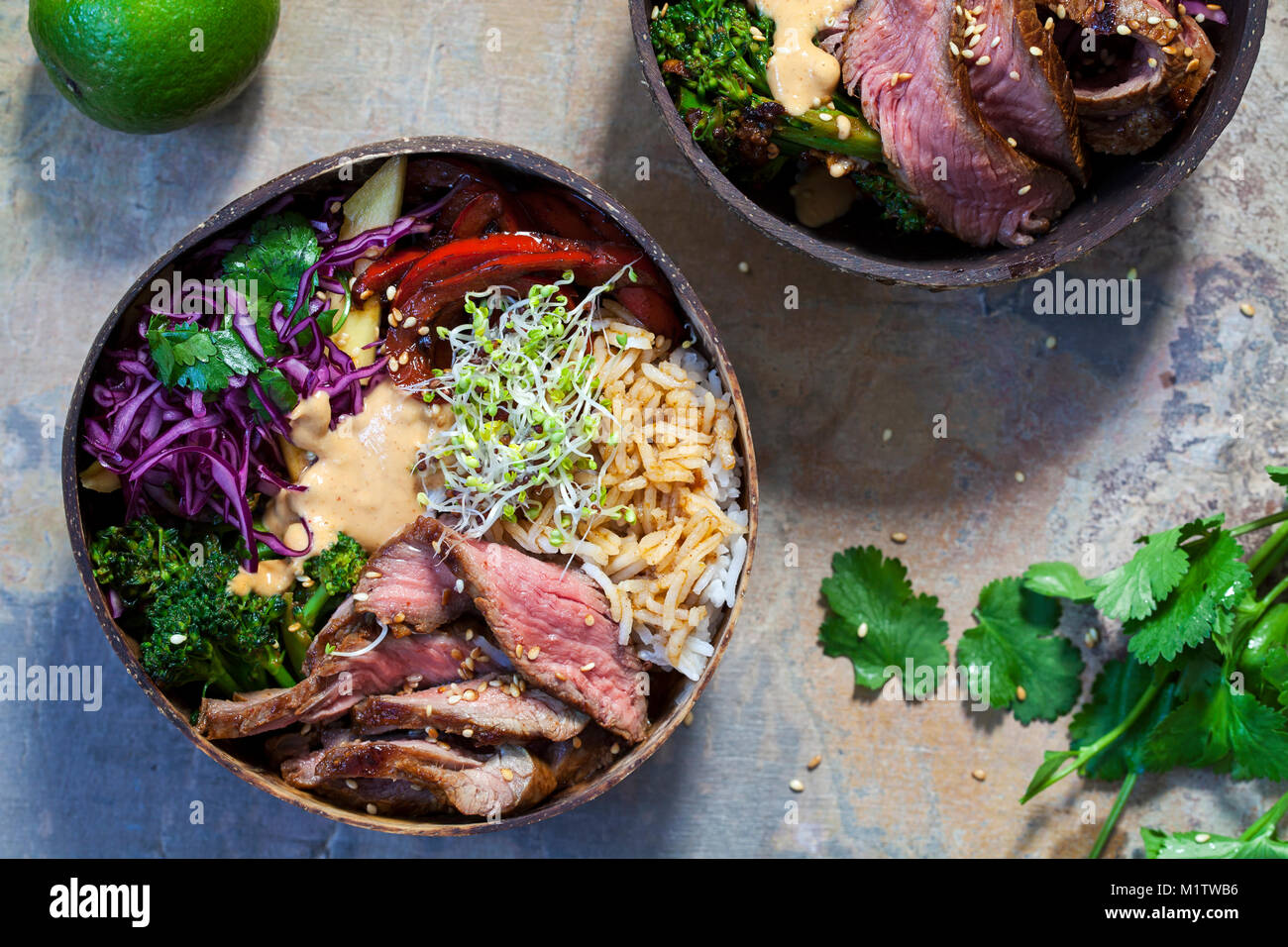 Bowl with sliced beef steak, broccoli, red cabbage, broccolli sprouts and satay sauce - Stock Image