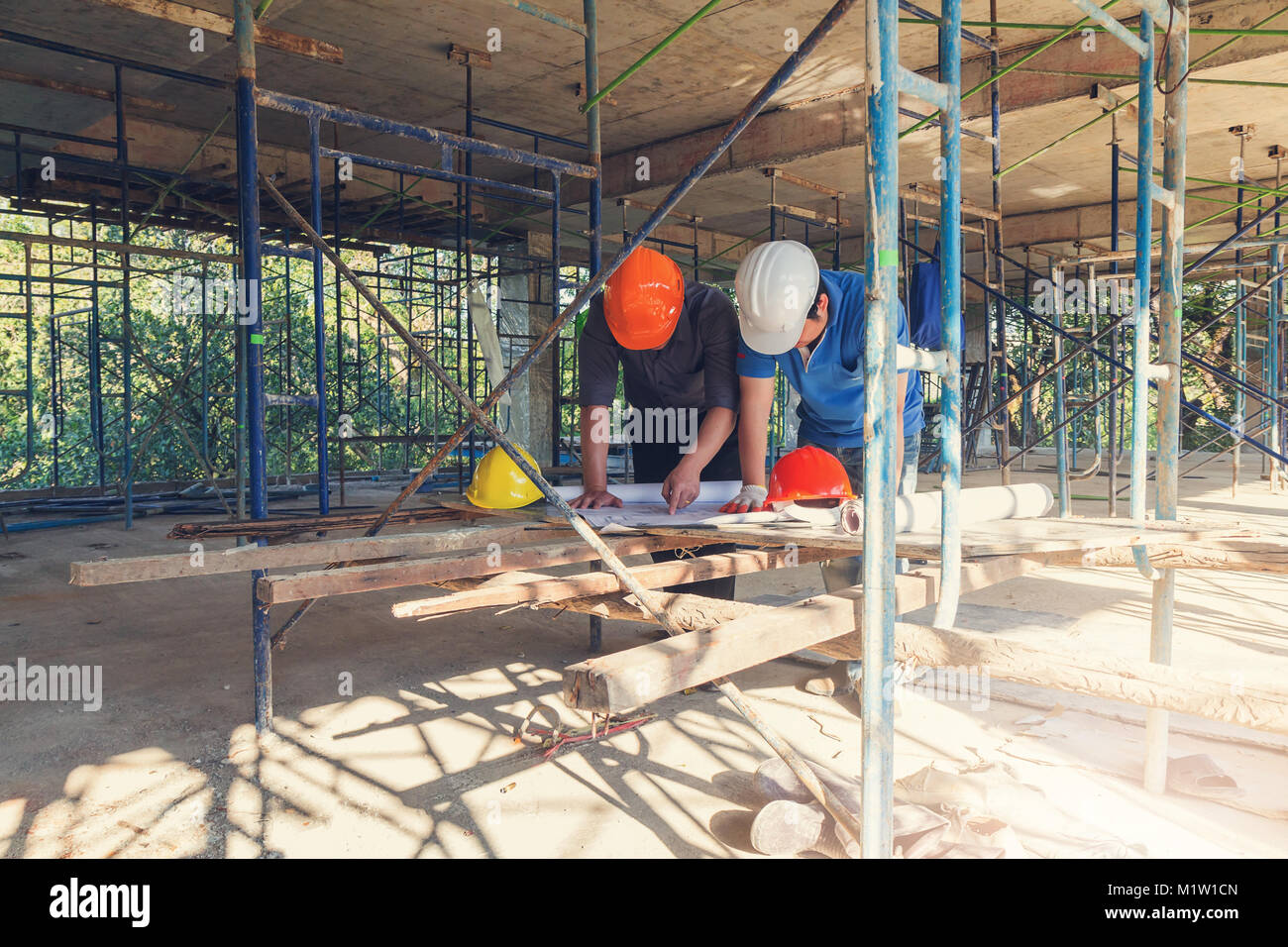 Construction concept of Engineer and Architect working at Construction Site with blue print - Stock Image